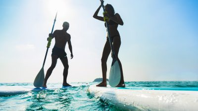 Stand Up Paddle Board Couple Paddleboarding . Young Caucasian Couple On Thailand Beach On Summer Holidays Vacation Travel.